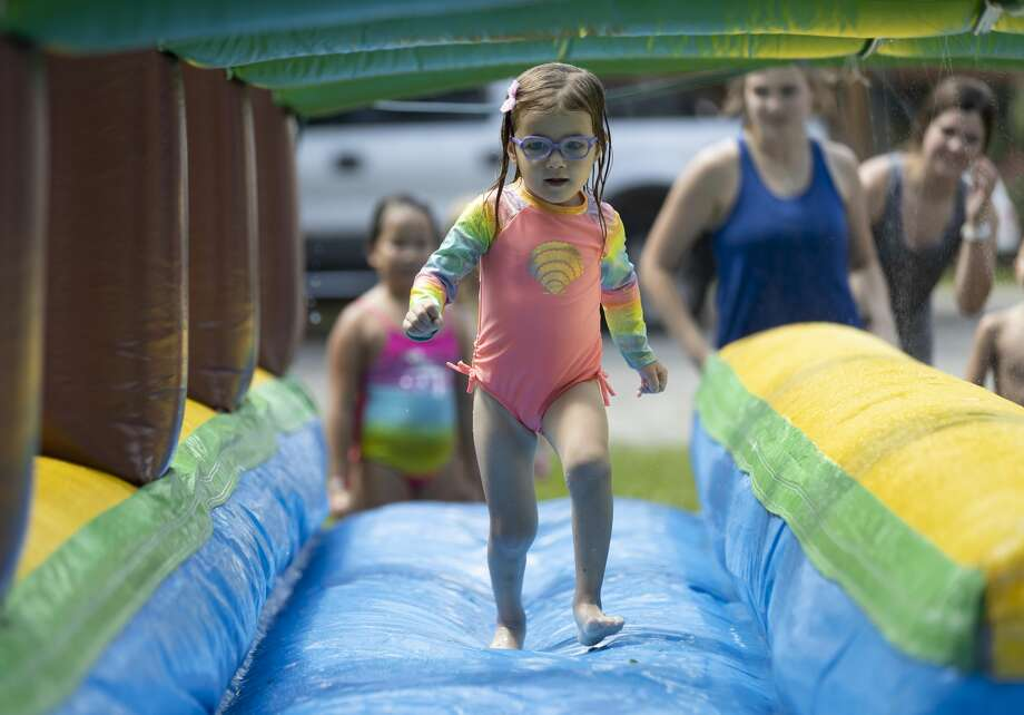 Brooke Lockler, 4, runs through a tunnel-like water slide during the City of Montgomery's Summer Water Party, Saturday, July 17, 2021, in Montgomery. The city hopes to host this event annually, as they started in 2019 but were unable to in 2020 due to the COVID-19 pandemic. Photo: Gustavo Huerta/Staff Photographer / Houston Chronicle © 2021