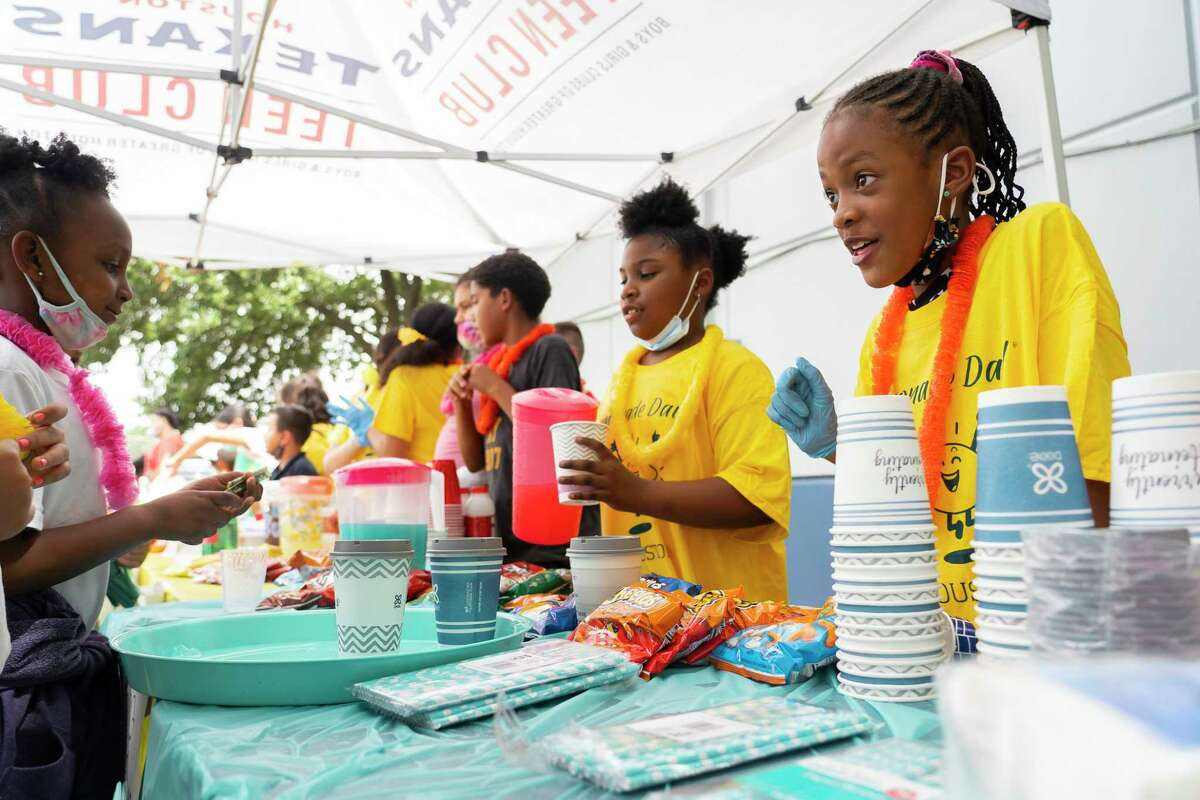 Eight-year-old Felicia, right, serves customers buying lemonade outside of the John and Cissy Harvard Boys and Girls Club of Greater Houston on Friday, July 16, 2021. The sale was the culmination of a business program the children had participated in with the organization Lemonade Day, which provides financial and entrepreneurship education for youth. The children participated in a month-long program this summer where they developed their lemonade stand business plan.