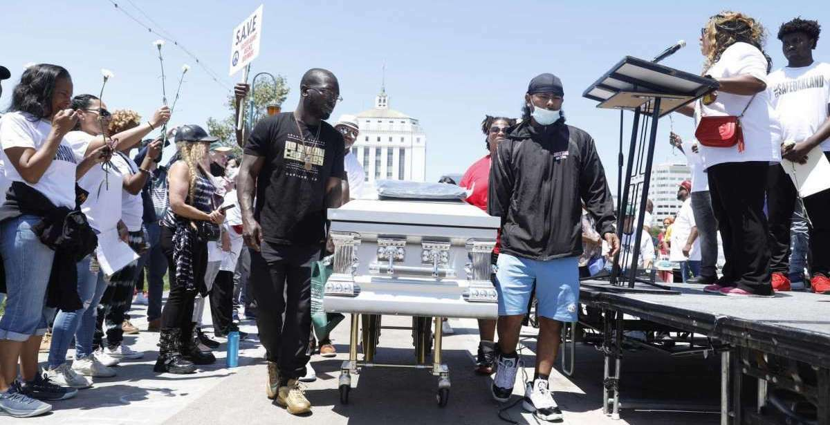Attendees of an anti-violence rally in Oakland on July 10 carry a symbolic coffin.