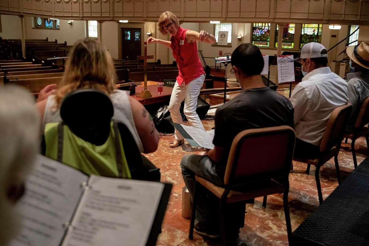Tracy Bjella Powers leads the Alamo City Street Choir during rehearsal at the Travis Park Church.