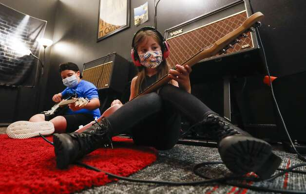 Olivia Shelton, right, plays her guitar beside Danny Slev during School of Rock'sRock 101 camp, Wednesday, July 14, 2021, in The Woodlands. Campers ages 7-12 explored instruments through musical games and activities during the five-day experience that ends with a concert on Friday. Photo: Jason Fochtman/Staff Photographer / 2021 © Houston Chronicle