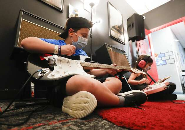 Danny Slev, left, plays his guitar beside Olivia Shelton during School of Rock'sRock 101 camp, Wednesday, July 14, 2021, in The Woodlands. Campers ages 7-12 explored instruments through musical games and activities during the five-day experience that ends with a concert on Friday. Photo: Jason Fochtman/Staff Photographer / 2021 © Houston Chronicle