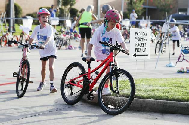 Triathletes transition to the biking portion as nearly 300 kids compete in the YMCA Kids Triathlon at The Woodlands Family YMCA at Branch Crossing, Saturday, July 17, 2021, in The Woodlands. Photo: Jason Fochtman/Staff Photographer / 2021 © Houston Chronicle