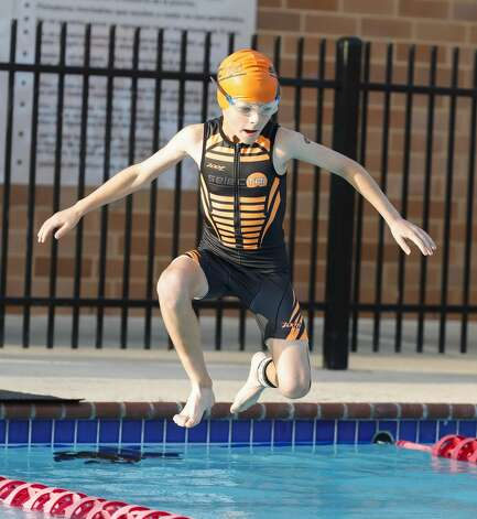 Carter Russell jumps into the pool as nearly 300 kids compete in the YMCA Kids Triathlon at The Woodlands Family YMCA at Branch Crossing, Saturday, July 17, 2021, in The Woodlands. Photo: Jason Fochtman/Staff Photographer / 2021 © Houston Chronicle