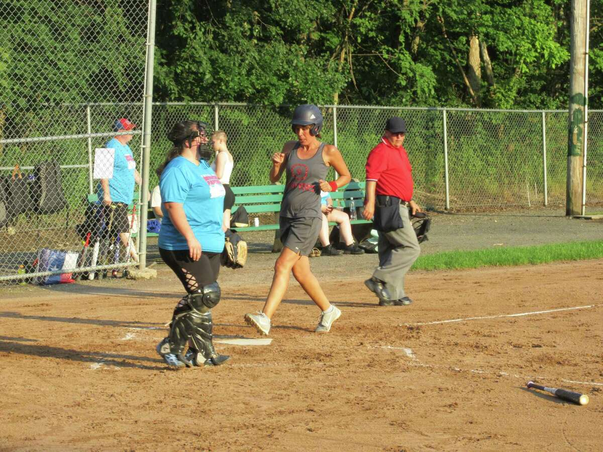 Stephanie Maxwell scores for her Sawyer's Girls team in the Torrington Parks and Recreation Softball League as Torrington Downtown Partners/USA Hauling catcher Linda Lafferty-Cerruto waits for another chance Thursday evening at Joe Ruwet Park.