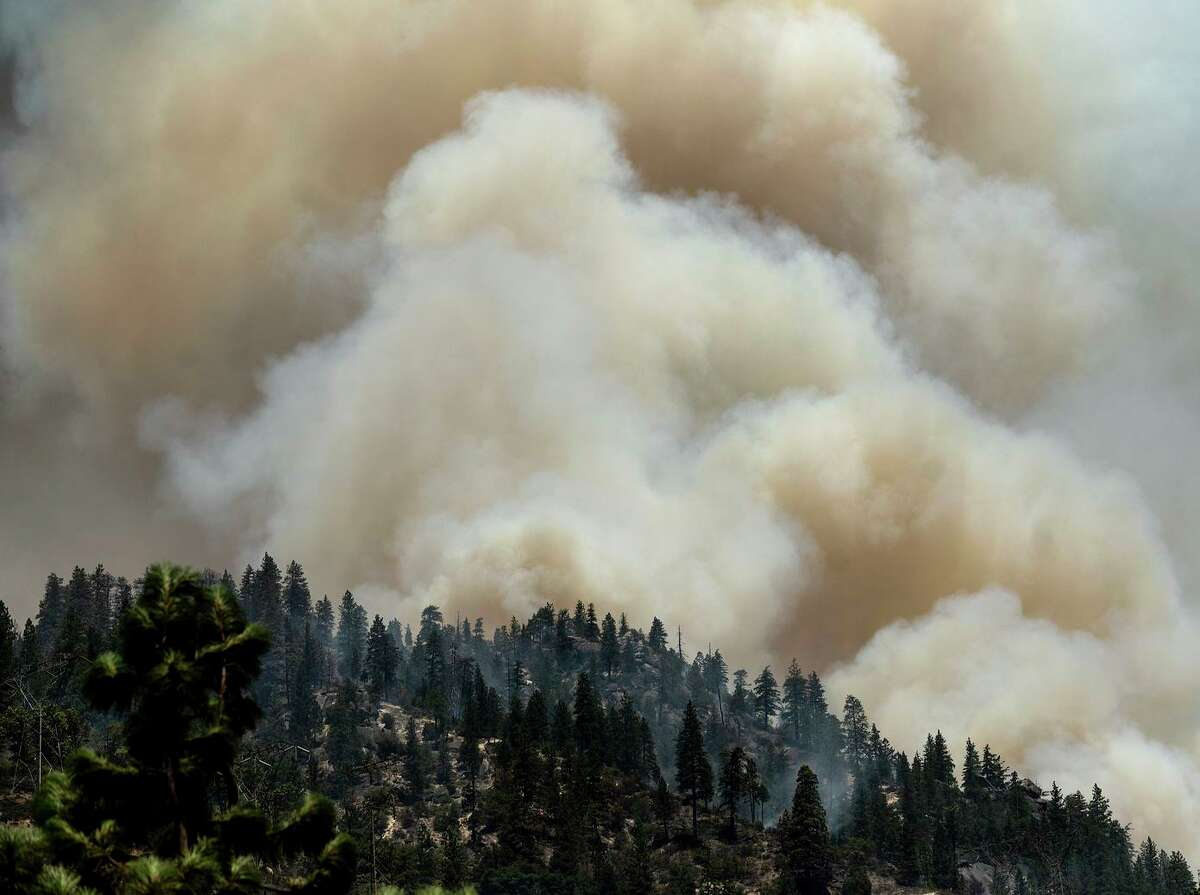 Smoke rises from the Dixie Fire burning along Highway 70 in the Plumas National Forest.