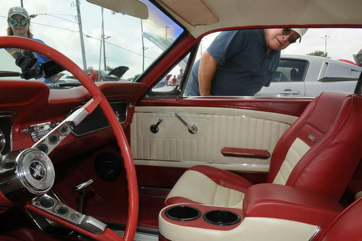 Chris Steuber of Alon admires the interior of a Mustang during Saturday's car show sat Roberts Ford in Alton. The Southern Illinois Mustang Association's Annual Mustang Round-up and All Ford Car Show is the longest continually ongoing show in the nation held at the same location.