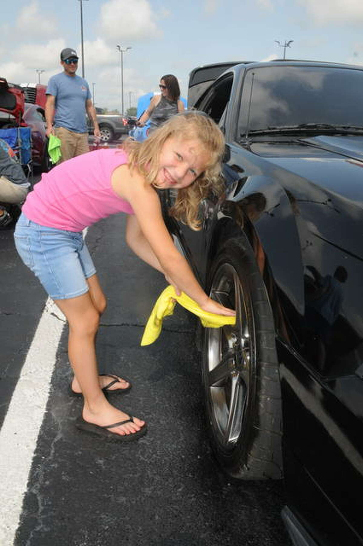 Six-year-old Kiersten Proffitt of Bethalto polishes her family's car during the 43rd Annual Mustang Round-Up and All Ford Car Show in Alton on Saturday.