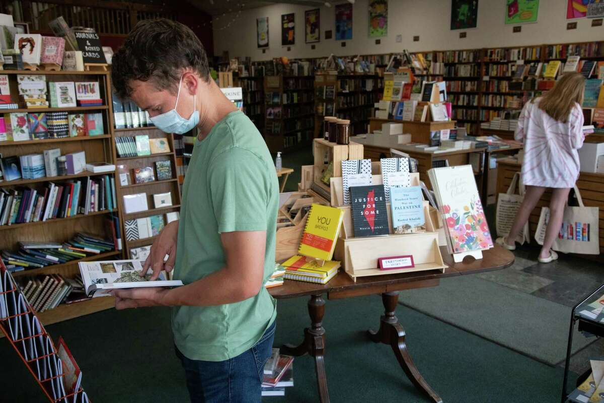 Thomas Gammer browses in a mask at Avid Reader in Davis. Yolo County recommends masks indoors.