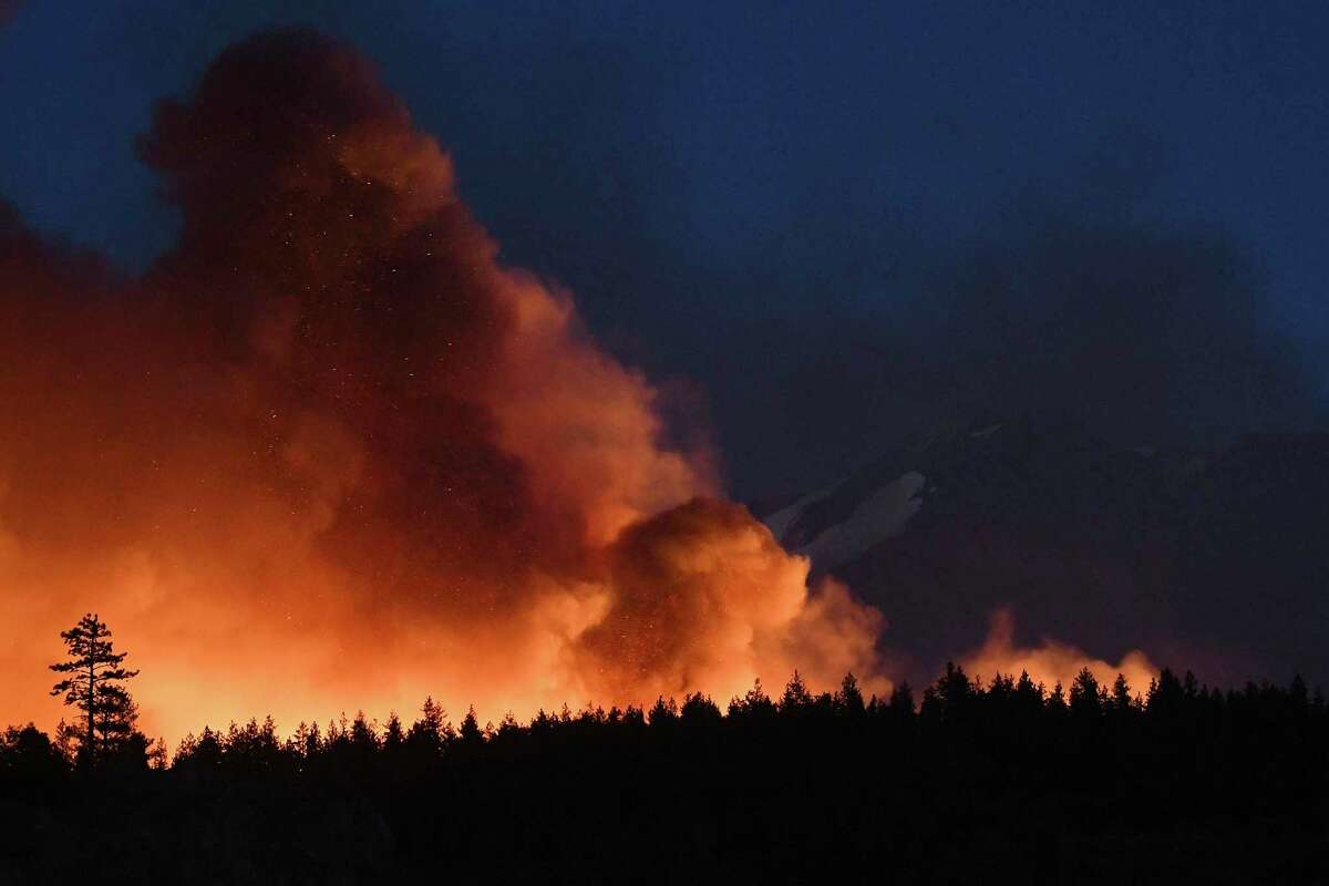 In this Monday, June 28, 2021, photo firefighters with the California Department of Forestry and Fire Protection work to extinguish hot spots after the Lava Fire burned through an area alongside U.S. Highway 97 northeast of Weed, Calif. (Scott Stoddard/Grants Pass Daily Courier via AP)