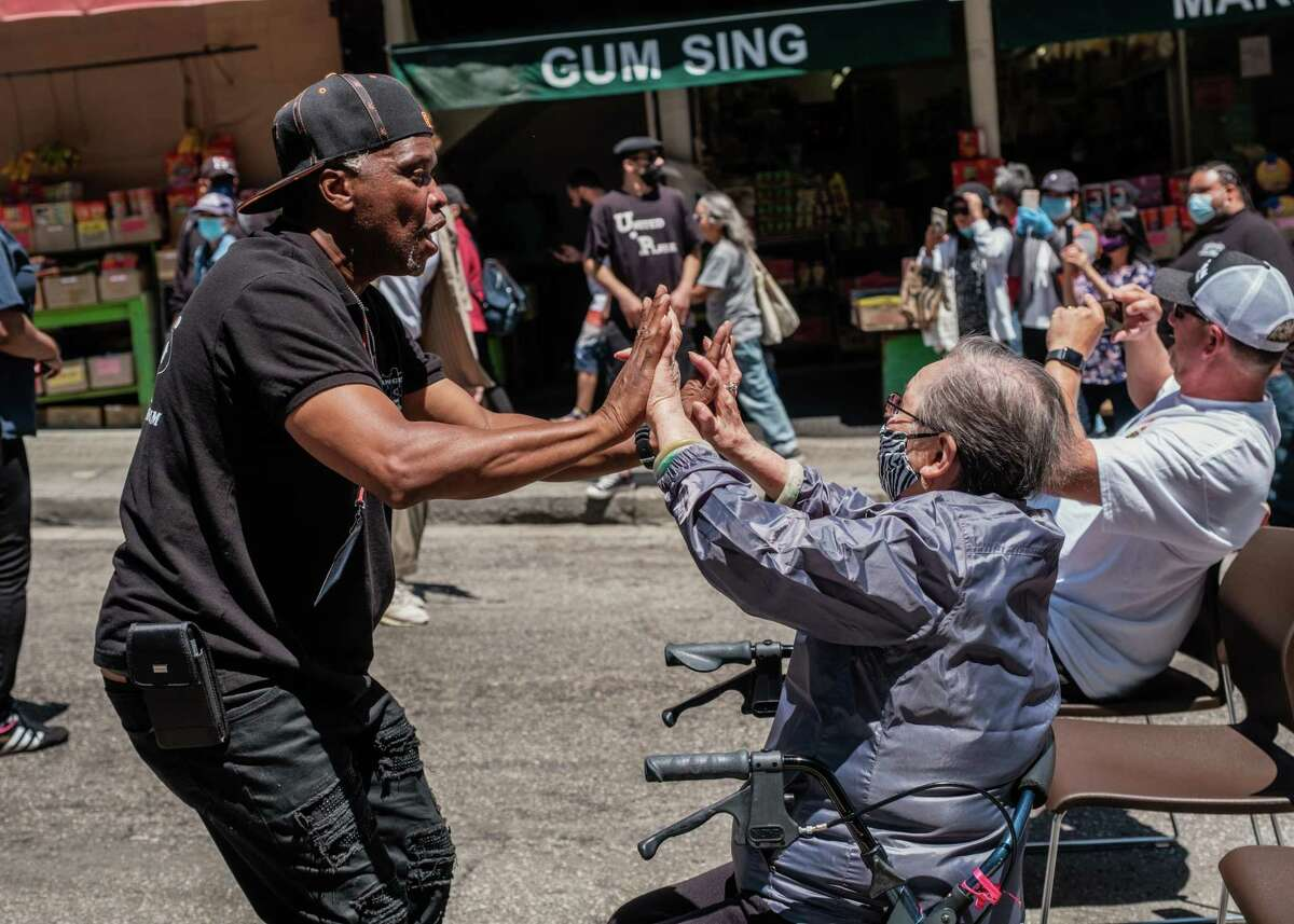 A gentlemen known as Guy from Hunters Point dances with Mrs. Lee Chang Jok at a Summer block party at Ping Yuen public housing project in the heart of San Francisco's Chinatown on Saturday, July 17, 2021.