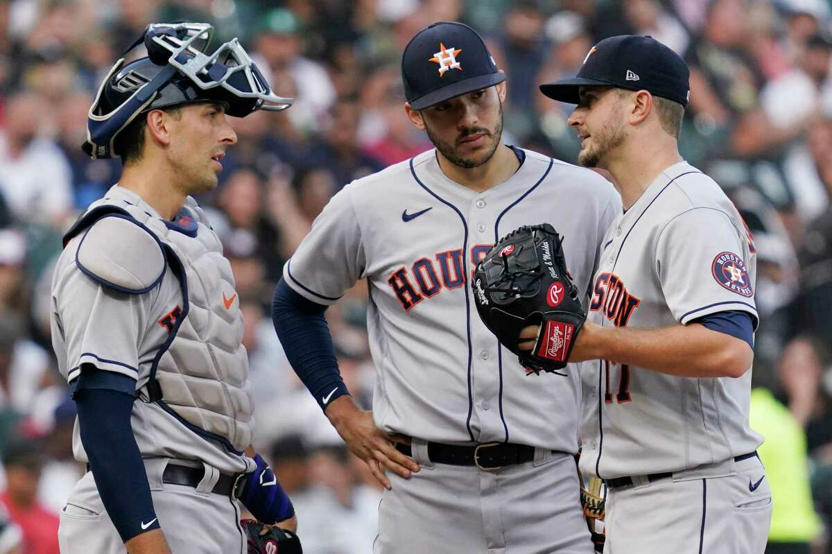 Houston Astros starting pitcher Jake Odorizzi, right, talks with catcher Jason Castro, left, and shortstop Carlos Correa during the third inning of the team's baseball game against the Chicago White Sox in Chicago, Saturday, July 17, 2021. (AP Photo/Nam Y. Huh)