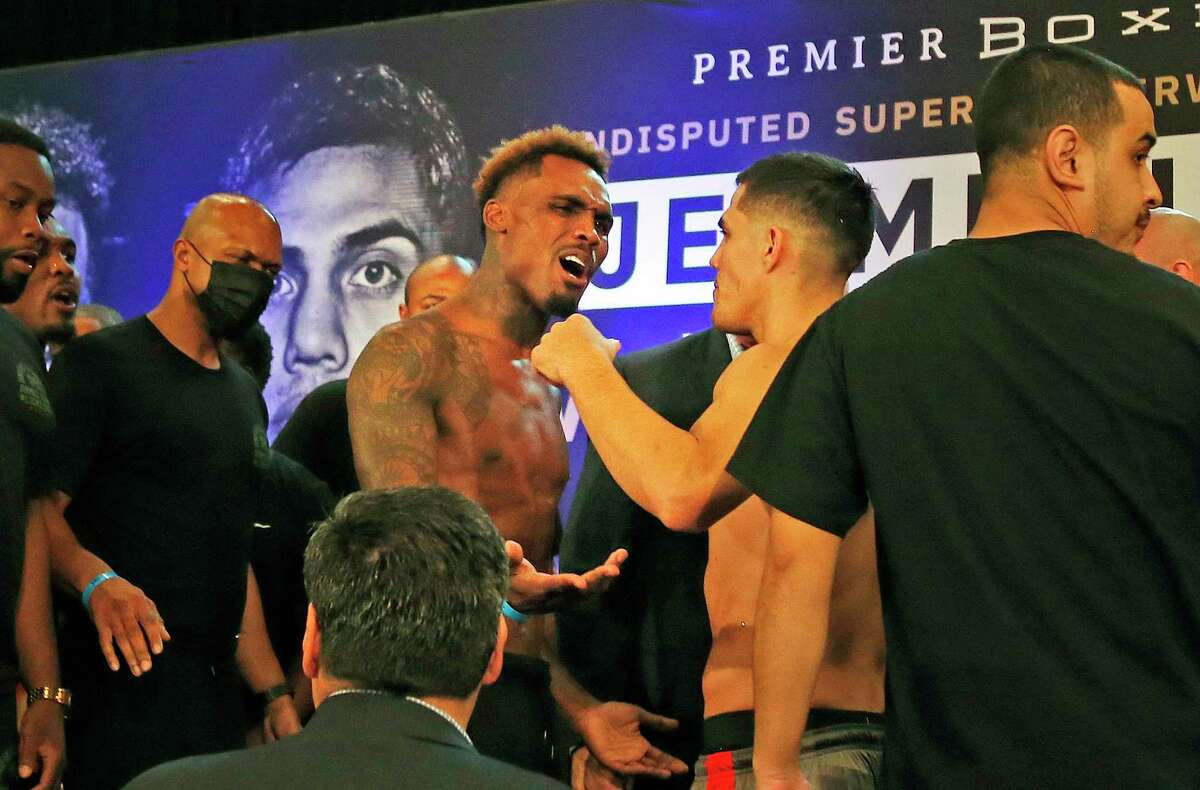Jermell Charlo, left, and Brian Castano engage in a war of words Friday before the stare-down photos of the official weigh-in for the undisputed 154-pound championship tonight at the AT&T Center.