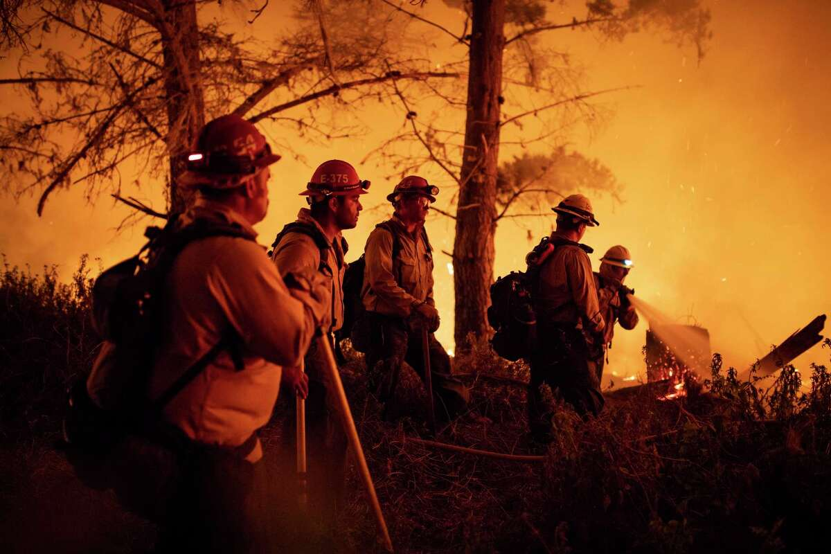 Cal Fire fighters and U.S. Forest Service firefighters battle a wildfire on the south coast of Big Sur, near Lucia (Monterey County), in August 2020.