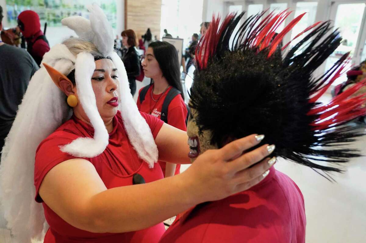 Natalie Macias of Lake Jackson helps her son, Micheal Lozano, 13, with his wig as they attend Comicpalooza at the George R. Brown Convention Center Saturday, July 17, 2021 in Houston. The multi-genre, comic book, science fiction, anime, gaming, and pop-culture convention continues through Sunday.
