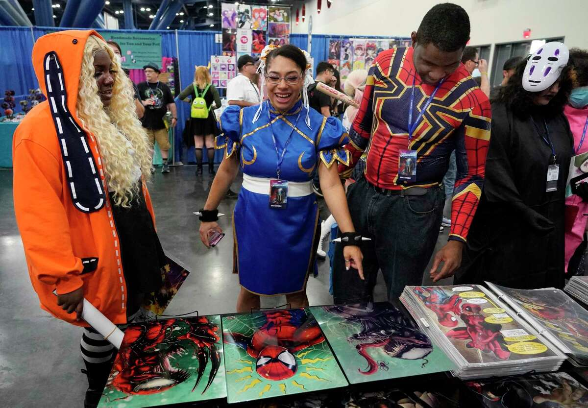 Sharice Bedford, left, Rachel Hollis, center, and her husband, Jon Hollis, right, look at a booth at Comicpalooza at the George R. Brown Convention Center Saturday, July 17, 2021 in Houston. The multi-genre, comic book, science fiction, anime, gaming, and pop-culture convention continues through Sunday.