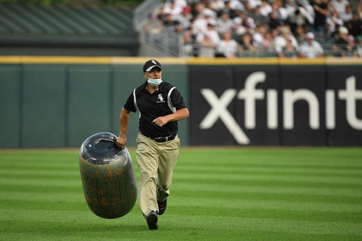 A member of Chicago White Sox grounds crew retrieves an item from the outfield during the fourth inning of the game between the Houston Astros and the Chicago White Sox at Guaranteed Rate Field on July 17, 2021 in Chicago, Illinois.