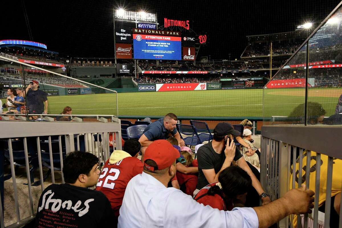Spectators take cover during a stoppage in play due to an incident near the ballpark during the sixth inning of a baseball game between the Washington Nationals and the San Diego Padres, Saturday, July 17, 2021, in Washington.