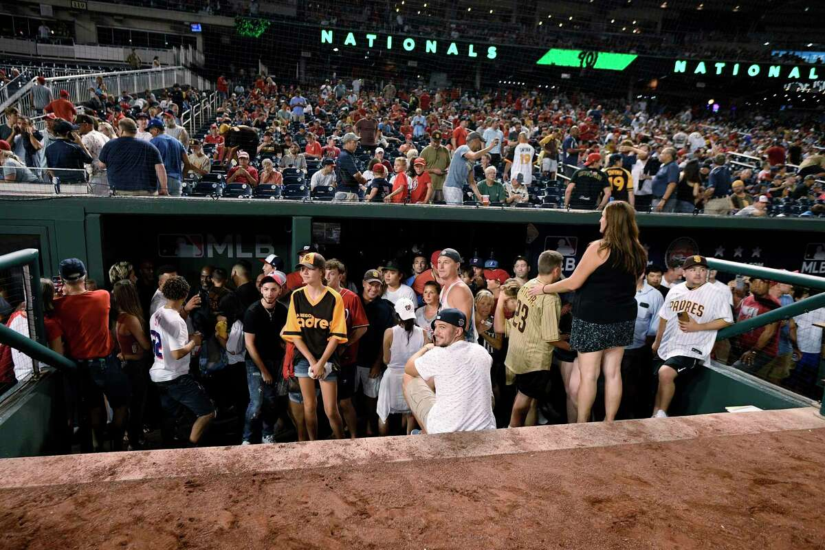 Spectators stand in the visiting team dugout during a stoppage in play due to an incident near the ballpark in the sixth inning of a baseball game between the Washington Nationals and the San Diego Padres, Saturday, July 17, 2021, in Washington.