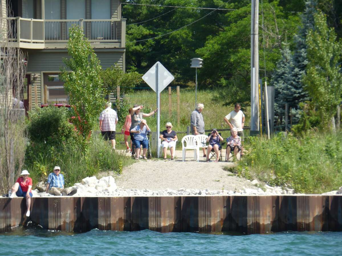 Residents gather to witness a dedication ceremony at Portage Lake channel.