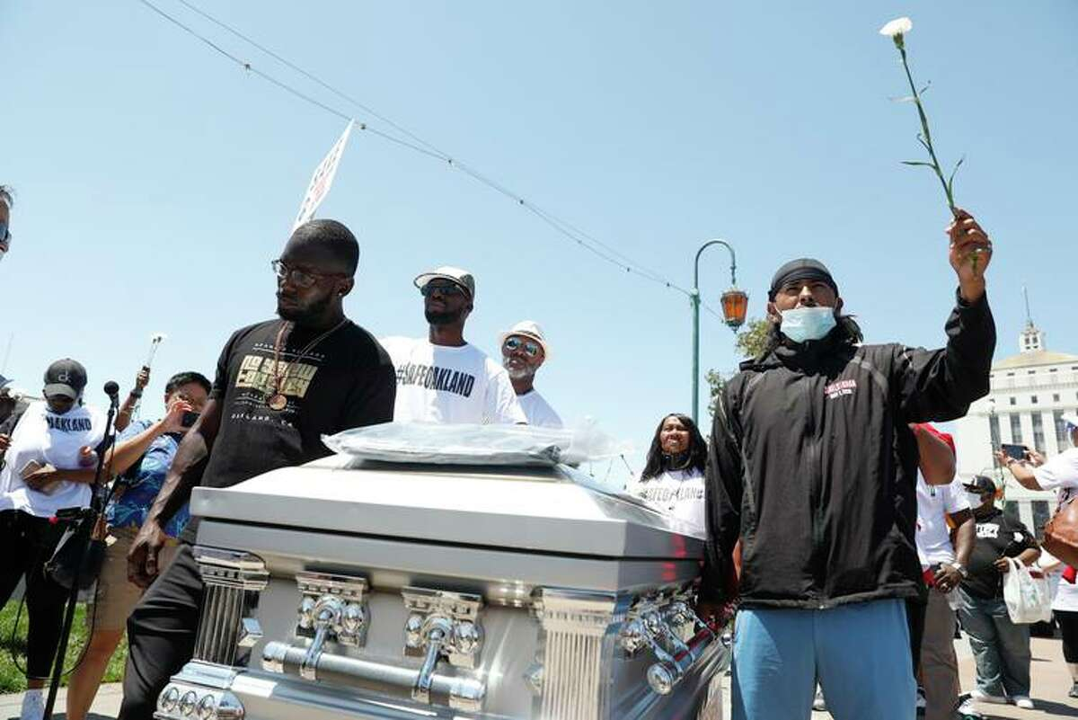 """Members of Adamika Village, a nonprofit that seeks solutions to violence, move a coffin symbolizing gun victims during a """"Stand Up for a Safe Oakland"""" rally on July 10."""