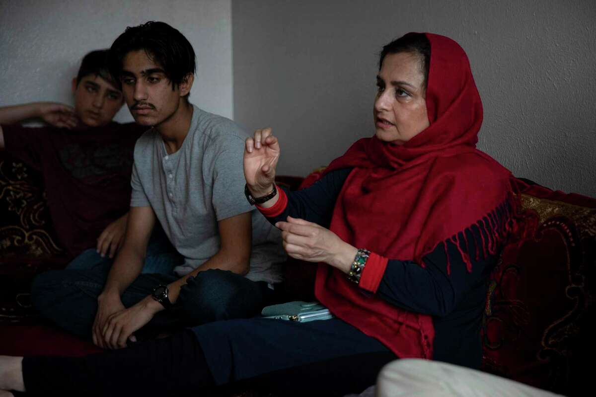 Farhana Khan, founder of Razakaar Foundation, helps refugees seek independence by providing access to health care, ESL classes and employment resources. Kahn, surrounded by the sons of Gultawarkhan Hussain Gu,y who arrived in Texas from Afghanistan 16 months ago, goes through basic instructions on dental care to help them prepare for a visit to the dentist.
