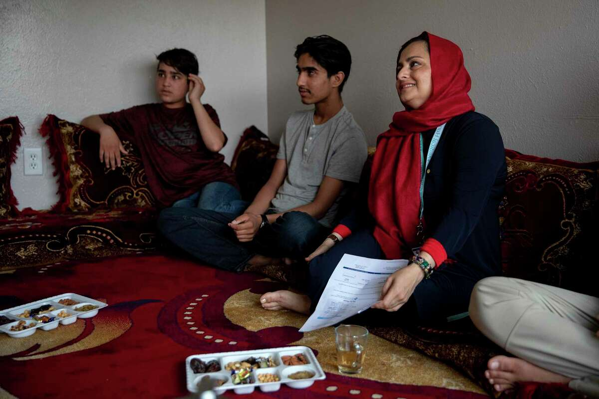 Farhana Khan, founder of Razakaar Foundation, helps refugees seek independence by providing access to health care, ESL classes and employment resources. Kahn, surrounded by the sons of Gultawarkhan Hussain Guy, who arrived in Texas from Afghanistan 16 months ago, helps him figure out how to navigate a medical bill.