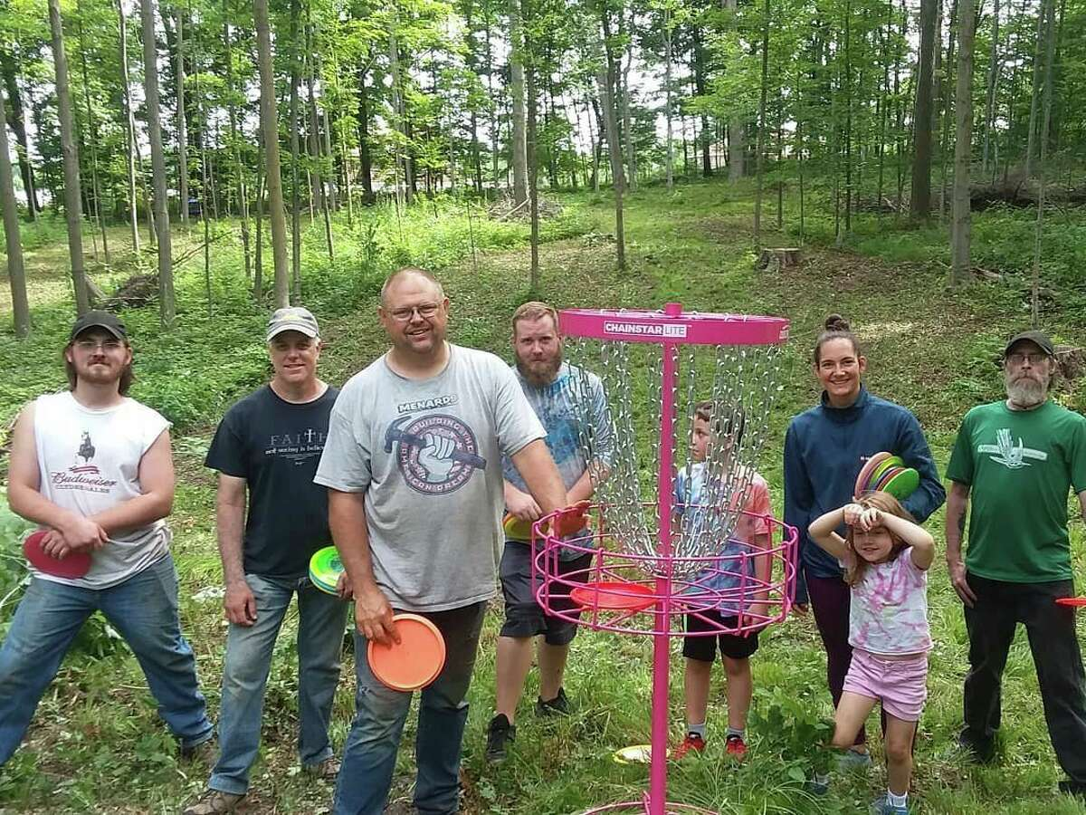 Volunteers help to clear thebrushin preparation for the disc gold courseat Rambadt Park in Reed City. Once a hole is cleared, a temporary basket is set up to do a dry run and see if further clearing needs done. (Submitted photo)