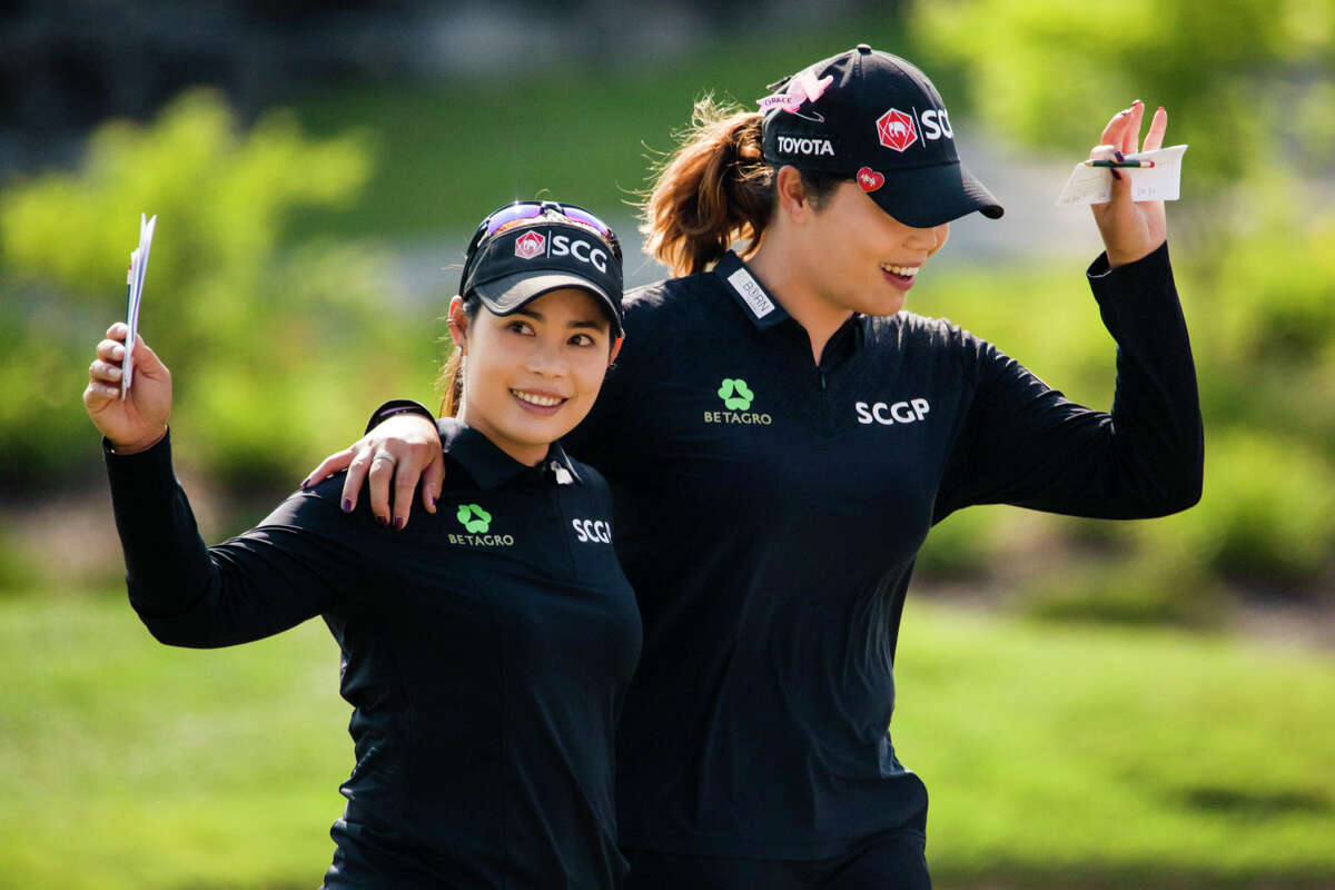 LPGA players Moriya Jutanugarn, left, and Ariya Jutanugarn, right, wave to the crowd following their final hole of play during the fourth and final round of play, securing their victory in the Dow Great Lakes Bay Invitational Saturday, July 17, 2021 at the Midland Country Club. (Drew Travis/for the Daily News)