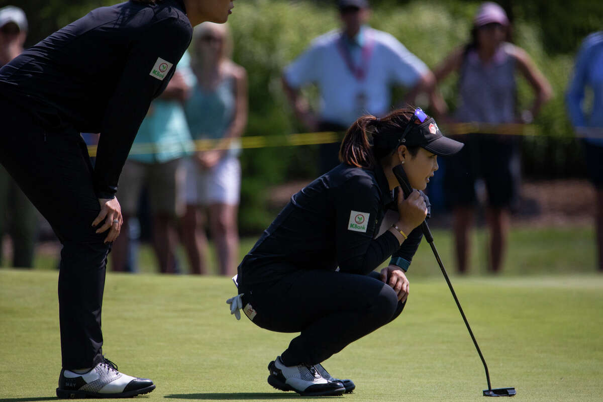 LPGA players Ariya Jutanugarn, left, and Moriya Jutanugarn, right, prepare for a putt during the fourth and final round of play in the Dow Great Lakes Bay Invitational Saturday, July 17, 2021 at the Midland Country Club. (Drew Travis/for the Daily News)