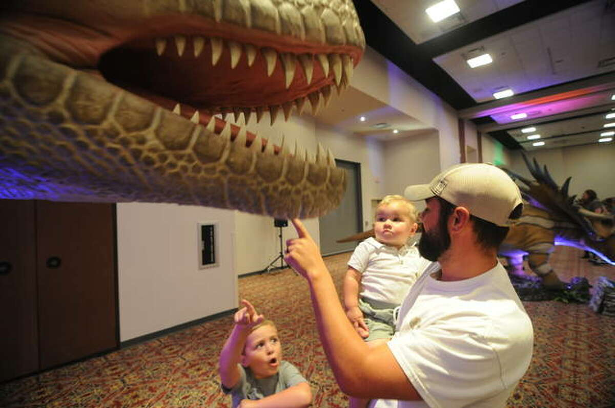 Corey Steber from Olney shows gives his sons Cooper and Rhett an up close and personal look at a dinosaur mouth Saturday. Din0 Stroll brought more than 70 dinosaurs to the Gateway Center in Collinsville this weekend.