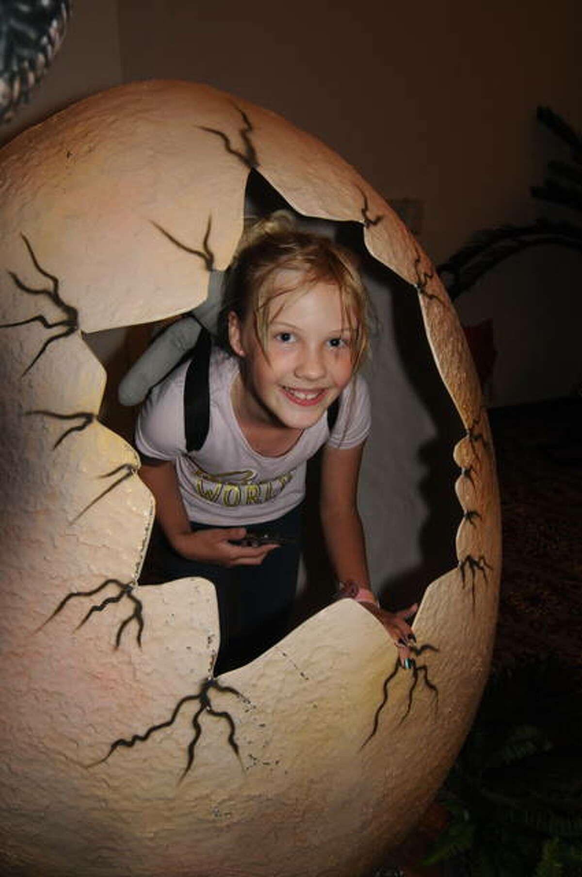 Nine-year-old Dakota Goodwin of Roseburg, Oregon, poses inside a dinosaur egg during the Dino Stroll in Collinsville Saturday.