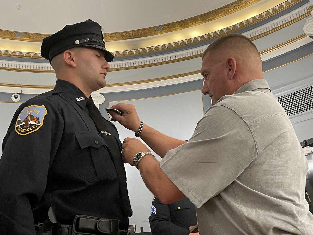 K9 Patrolman Sean Clifford (Ret.) pins a badge on the uniform of his son, Patrolman Joshua Clifford, who was sworn into the Schenectady Police Department on July 7, 2021.
