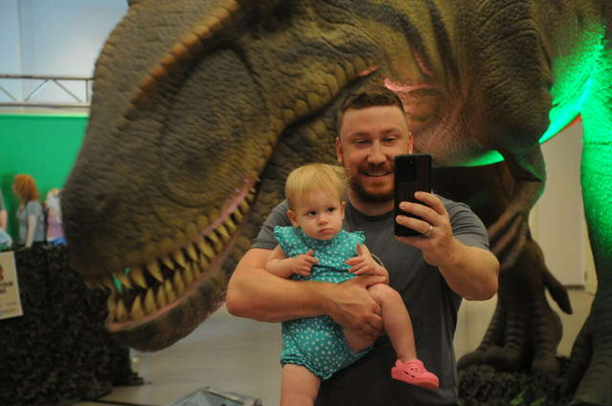 Joella Toigo, 19 months, of Edwardsville endures a selfie her father Andrew takes Saturday with a T-Rex during the Dino Stroll in Collinsville.