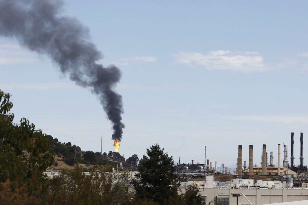 Smoke and flames shoot from a building after a release of chemicals at the Chevron oil refinery in Richmond in August.