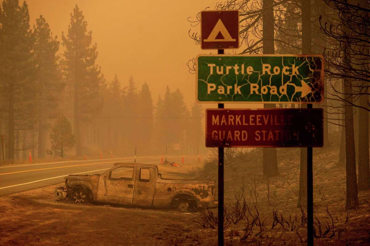 A scorched car rests on a roadside as the Tamarack Fire burns Saturday in Markleeville (Alpine County). Smoke from the Tamarack Fire briefly made for very unhealthy air quality.