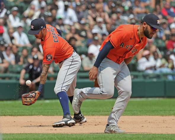 CHICAGO, ILLINOIS - JULY 18: Carlos Correa #1 of the Houston  Astros bobbles the ball as Abraham Toro #13 runs past him allowing a single to Andrew Vaughn of the Chicago White Sox in the 5th inning at Guaranteed Rate Field on July 18, 2021 in Chicago, Illinois. Photo: Jonathan Daniel, Getty Images / 2021 Getty Images