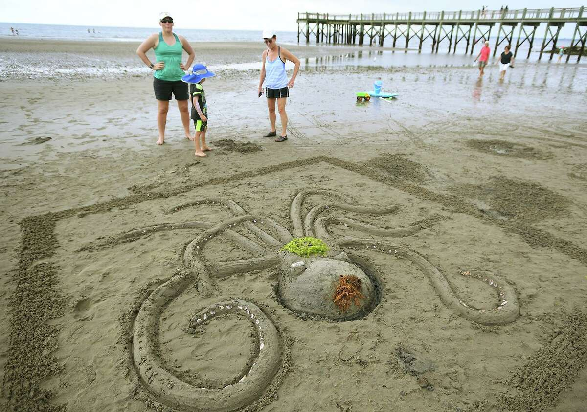Kate Zinsser, of Oak Park, Illinois, her son Graeson, 5, and mother-in-law Jane MacAlpine, of Milford, admire their finished octopus sand sculpture during the annual sand sculpture competition at Walnut Beach in Milford Conn. on Sunday, July 18, 2021. Live judging was canceled for fear of rain, but contestants were still able to submit photographs of their finished sculptures for judging in a virtual competition.