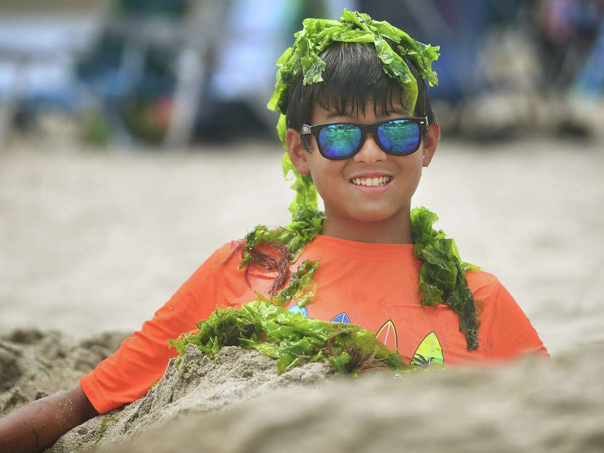 James Lee, 14, of Milford, goes the extra mile burying himself in the sand and covered in seaweed to portray a merman during the annual sand sculpture competition at Walnut Beach in Milford on Sunday. Live judging was cancelled for fear of rain, but contestants were still able to submit photographs of their finished sculptures for judging in a virtual competition. See more photos on A3.
