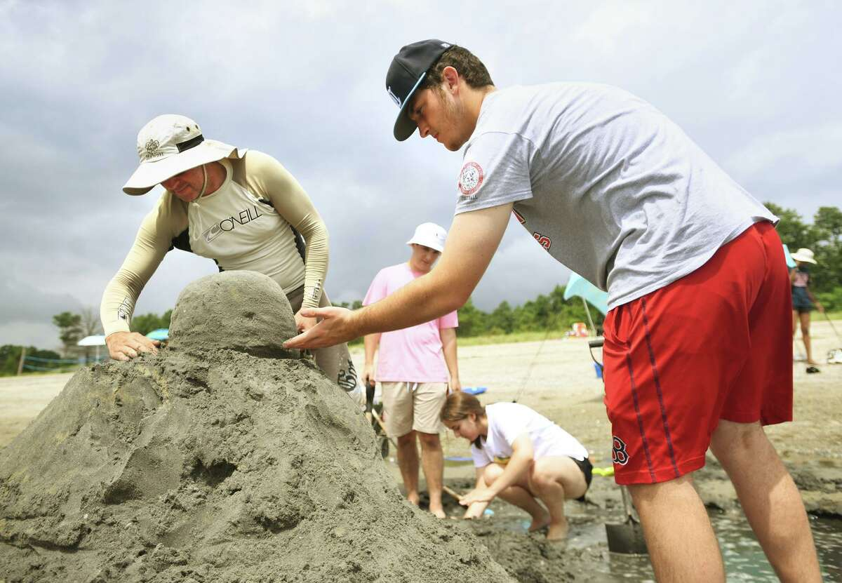 Milford Robotic Club leader Chris Seluga, left, and club member Joe Gaetano, 16, of Milford, sculpt the head of their Lego person riding a paddle board sand sculpture during the annual sand sculpture competition at Walnut Beach in Milford Conn. on Sunday, July 18, 2021. Live judging was cancelled for fear of rain, but contestants were still able to submit photographs of their finished sculptures for judging in a virtual competition.