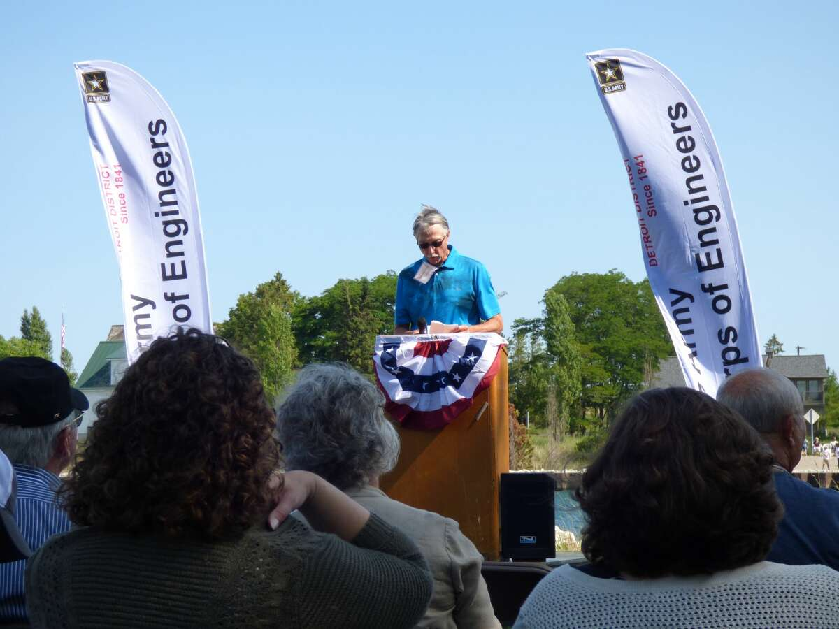 Onekama township supervisor David Meister welcomes local officials and residents to a Portage Lake channel dedication.