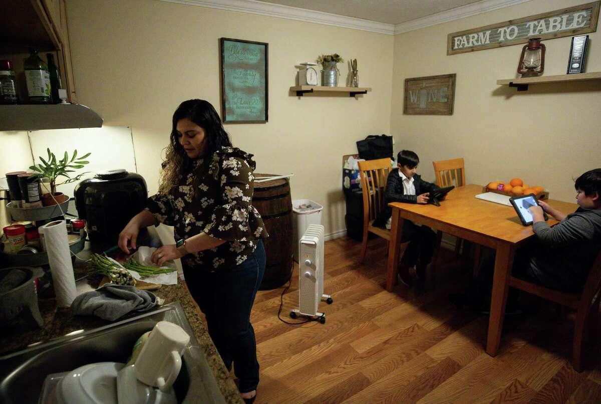 Vanessa Rodriguez, left, prepares dinner for her family at their home Wednesday, Feb. 3, 2021, in Crosby, Texas. Rodriguez, from Mexico, has been thinking about applying for DACA for many years, but it wasn't until president Joe Biden took office that she finally felt safe to do so. As a mother of three American children, she was afraid of giving her information to the government and being deported. Now she and her husband are among the many DACA eligible people that are applying for the first time.