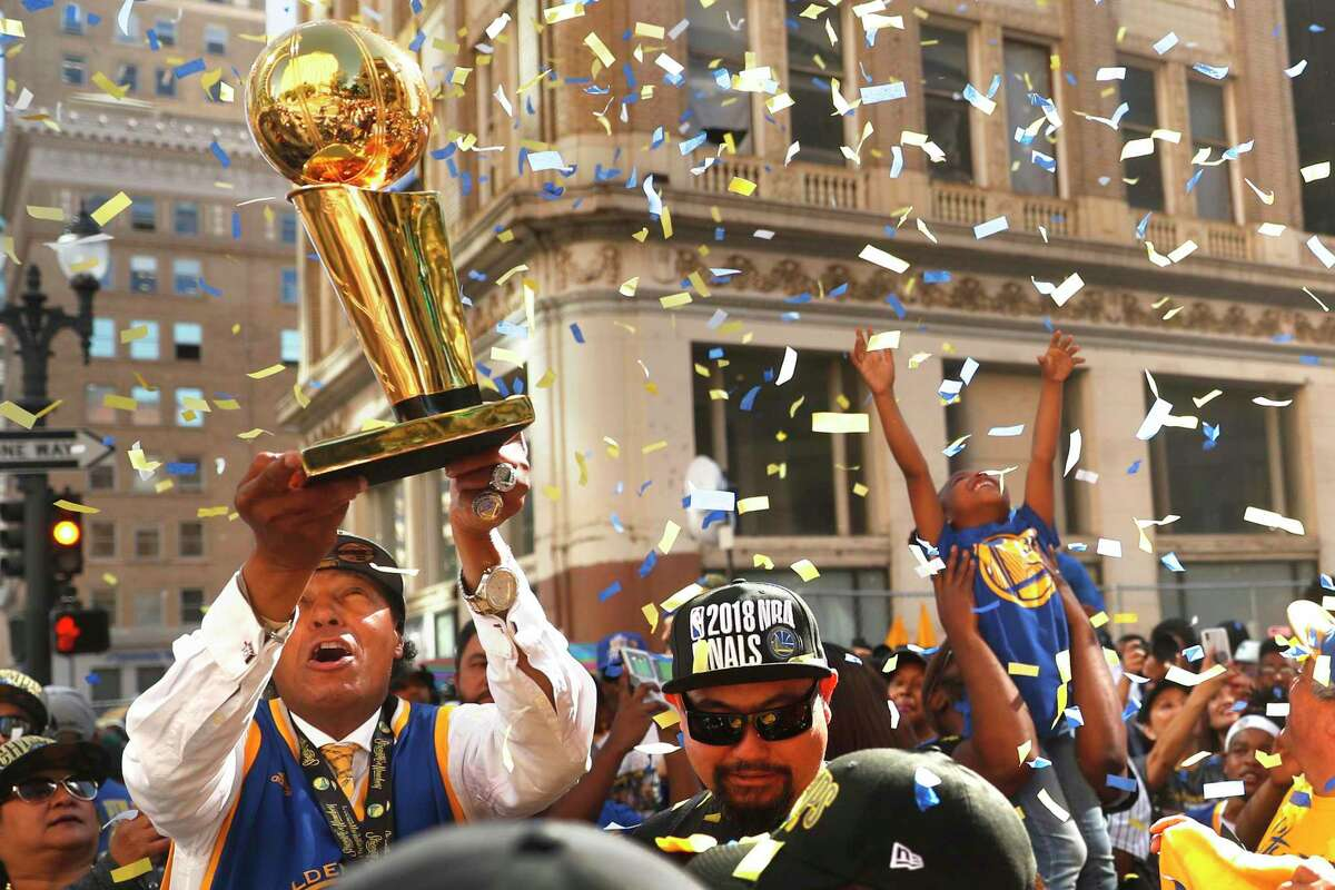 Charles Chapman of Oakland holds up a replica Larry O'Brien trophy as fans create their own confetti celebration before Golden State Warriors' NBA Championship parade in Oakland, CA on Tuesday, June12, 2018.What does it mean to be a Warriors fan at a time of unprecedented team dominance and unprecedented local dissatisfaction?