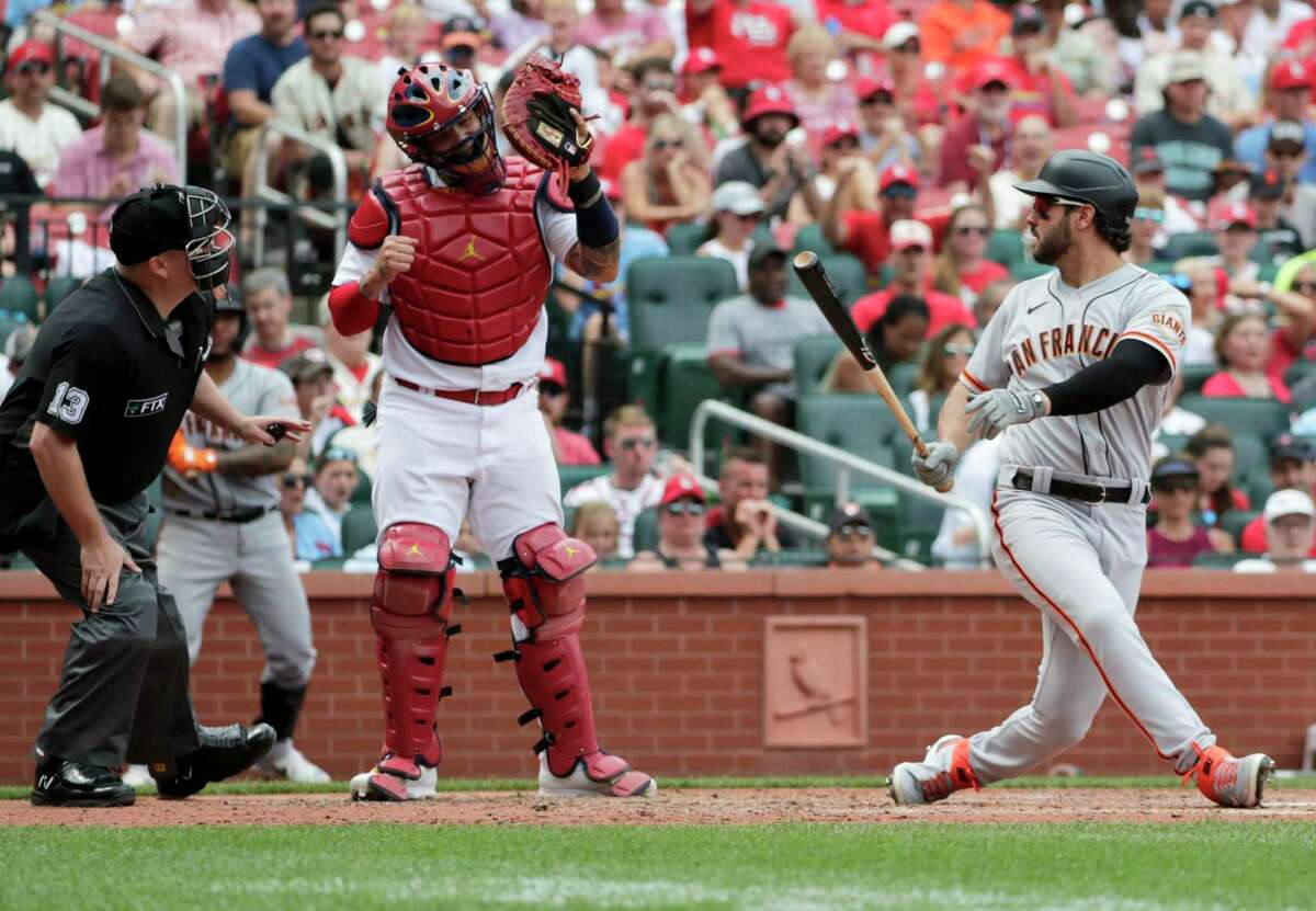 St. Louis Cardinals catcher Yadier Molina, center, celebrates after San Francisco Giants' Mike Tauchman, right, struck out with the bases loaded while home plate umpire Todd Tichenor, left, make sure he caught the ball in the sixth inning of a baseball game, Sunday, July 18, 2021, in St. Louis. (AP Photo/Tom Gannam)