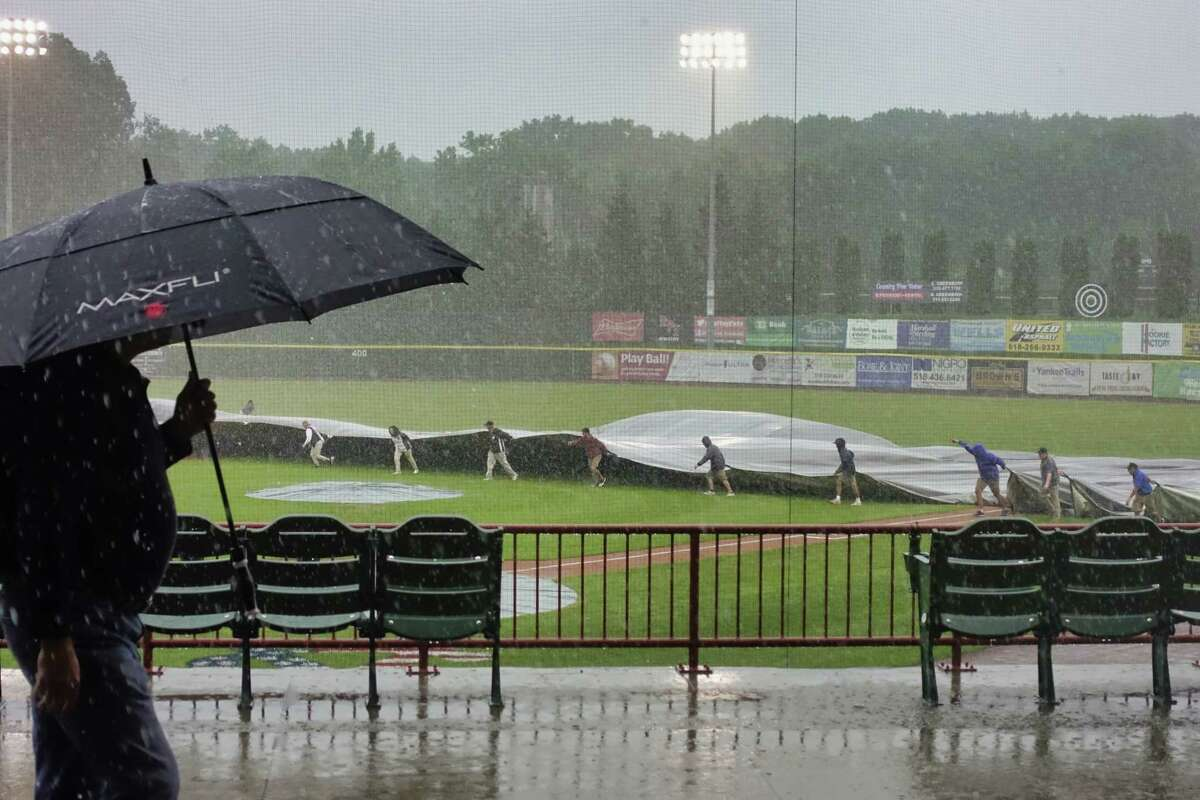 Grounds crew members pull a covering onto the infield as heavy rain began to fall during the Tri-City ValleyCats game against Equipe Quebec on Sunday, July 18, 2021, in Troy, N.Y. More rain is expected Sunday, Aug. 1, 2021. (Paul Buckowski/Times Union)