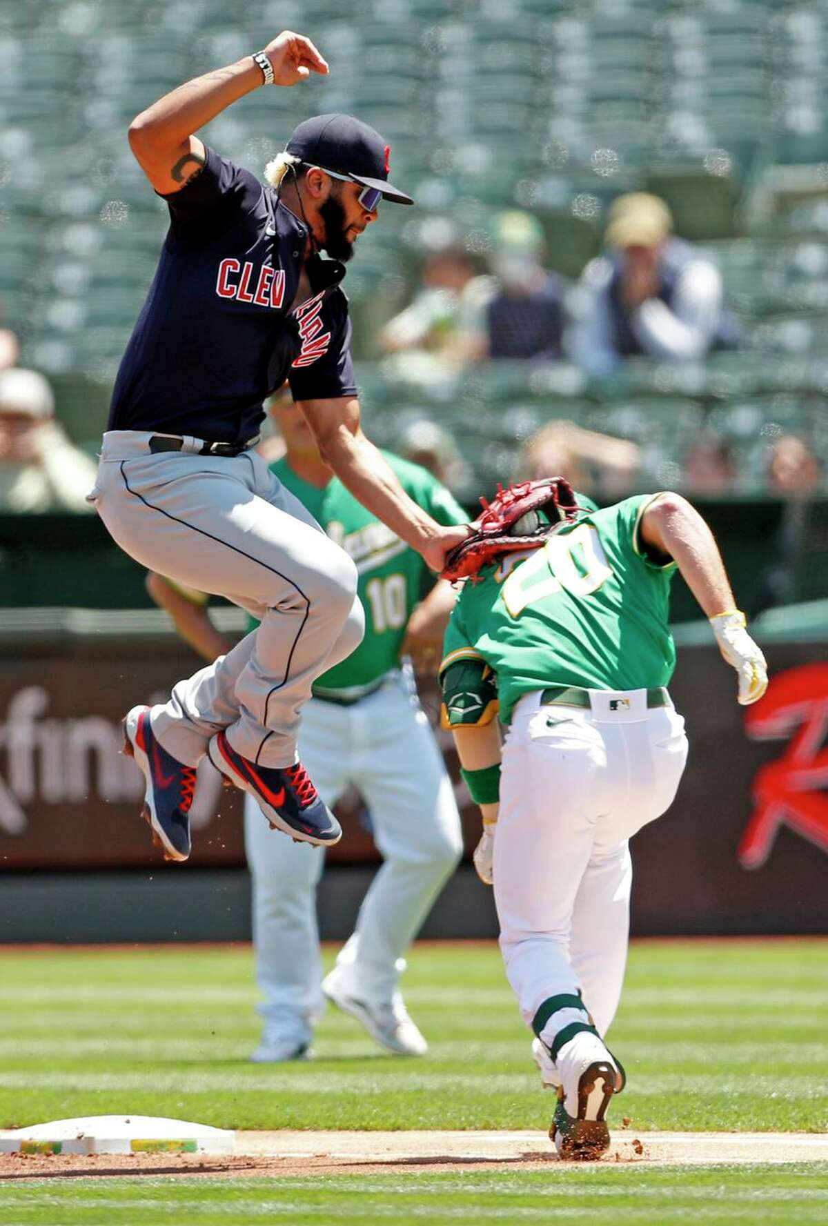 A's slugger Mark Canha is tagged out by Indians first baseman Bobby Bradley during the first inning at Oakland Coliseum.