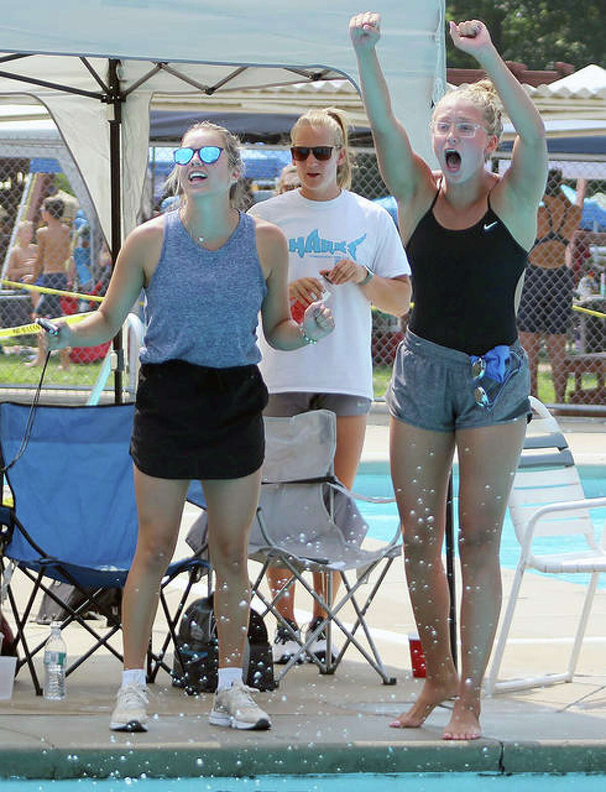 Summers Port assistant swim coaches Ginny Schranck, left and Anna Moehn, right, cheer on their swimmers Sunday as head coach Maddie Monroe, center, looks on.