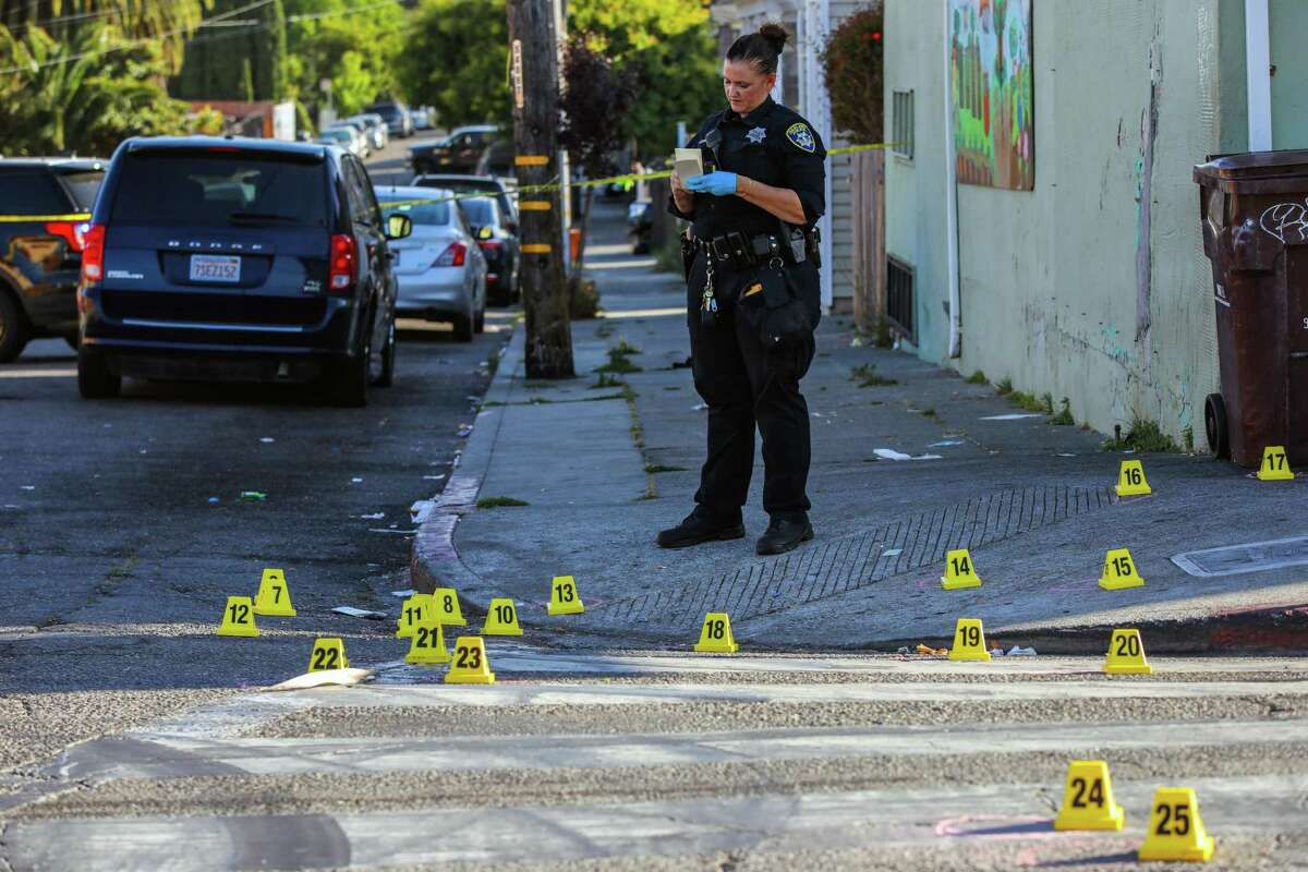 An officer investigates a fatal June shooting in Oakland, where money is being shifted from police to violence prevention.