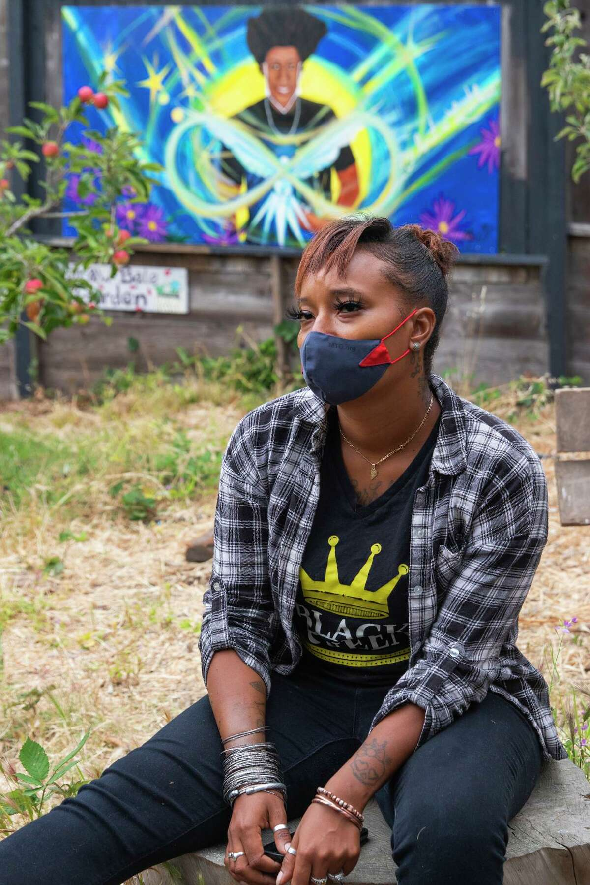 Sequence Young, program coordinator at the Berkeley Alternative Resource Center, sits near a mural of her former intern Demetrius Fleming-Davis, who was killed in East Oakland in April.