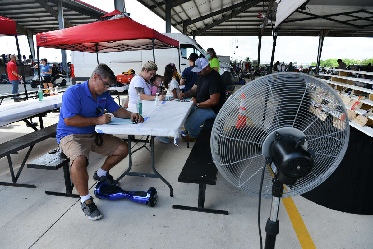 Travis Drescher, Zha-Zha Barajas and her husband Eric fill out paperwork during a Metro Health pop up COVID vaccine clinic at Traders Village Sunday. Those who chose to get shots were administered the Johnson & Johnson vaccine.
